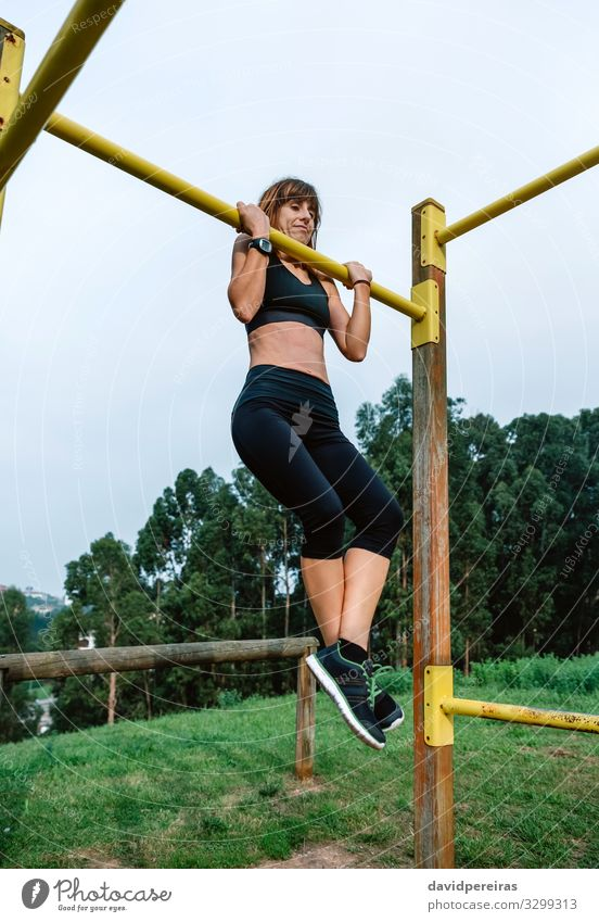 Sportlerin bei Klimmzugübungen Lifestyle Körper Mensch Frau Erwachsene Arme Natur Park Turnschuh Fitness hängen dünn stark Kraft anstrengen Energie Athlet