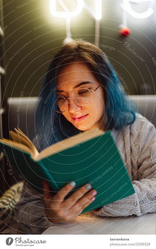 Junge Erwachsene gemischte asiatische Frau mit blauen Haaren hält ein Buch in einem Café mit Neonlicht, selektiver Fokus Beautyfotografie bunte Haare Gesicht