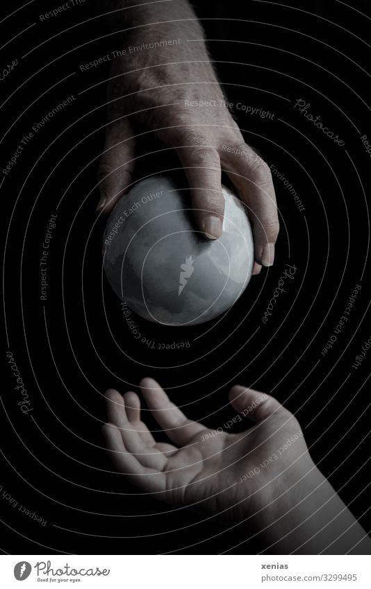 reife Hand übergibt grauen Globus an junge Hand Erdkugel Finger Umwelt Erde Klima Klimawandel schwarz Verantwortung Zukunftsangst Endzeitstimmung bedrohlich