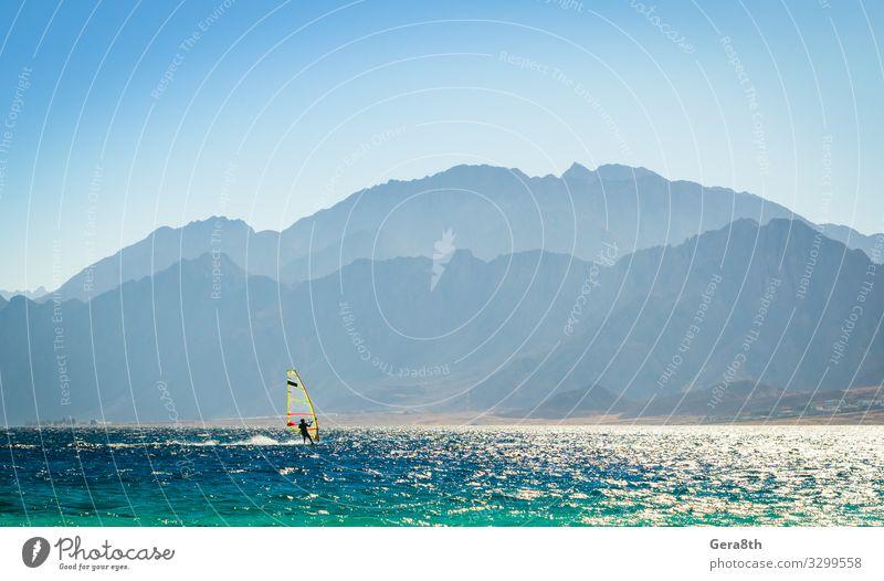 Surfer reitet in Ägypten ins Meer Dahab Erholung Ferien & Urlaub & Reisen Tourismus Insel Wellen Berge u. Gebirge Sport Natur Landschaft Wind Felsen Küste Segel