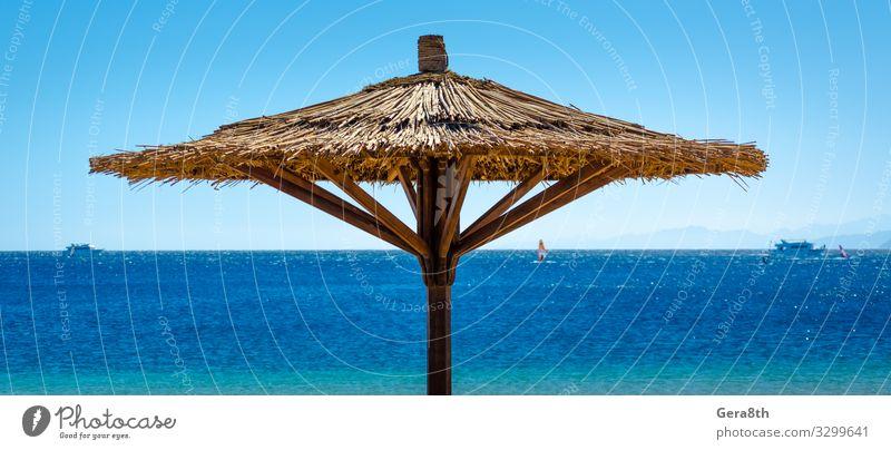 Schilfstrandschirme gegen das blaue Meer in Ägypten Erholung Ferien & Urlaub & Reisen Tourismus Sommer Strand Berge u. Gebirge Natur Landschaft Himmel Horizont