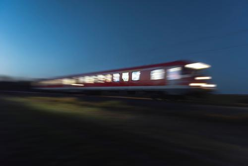 Der Zug fährt nachts. Der Bewegungszug verschwimmt. Reisen bei Nacht Ferien & Urlaub & Reisen Verkehr Personenverkehr Öffentlicher Personennahverkehr Bahnfahren