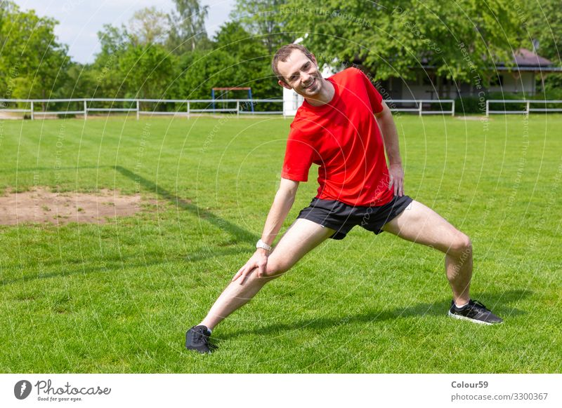 Dehnungsübung Lifestyle Wellness Freizeit & Hobby Sport Sportler Fußballplatz Mensch maskulin Junger Mann Jugendliche Natur Bewegung Fitness Blick
