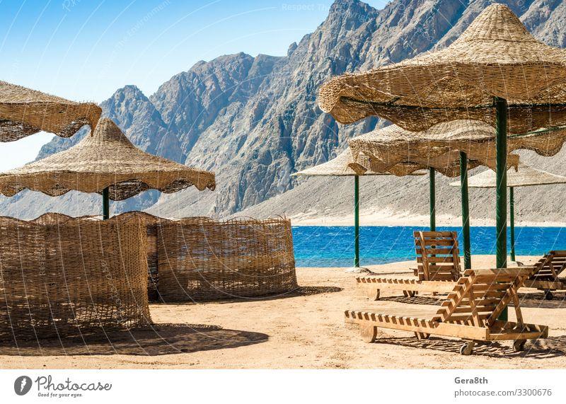 Sonnenschirme und Liegestühle am Strand in Ägypten Erholung Ferien & Urlaub & Reisen Tourismus Sommer Meer Berge u. Gebirge Sand Himmel Felsen Küste Holz heiß
