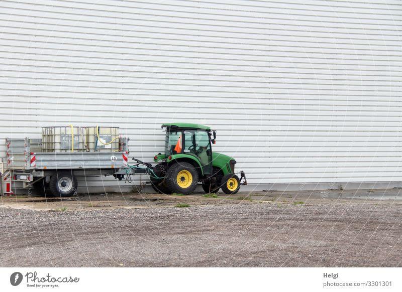 Traktor mit Anhänger steht vor einer weißen Wand Hafenstadt Platz Fassade Stein Metall Kunststoff stehen warten authentisch einzigartig braun gelb grau grün