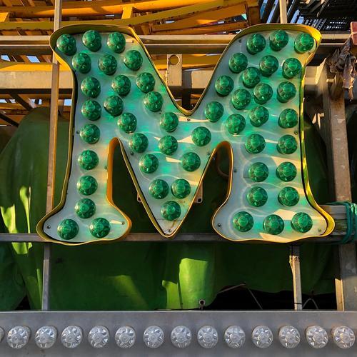 M Schriftzeichen grün Farbe Freude Idee Kommunizieren Kreativität Lebensfreude Jahrmarkt Glühbirne Lateinisches Alphabet Farbfoto Außenaufnahme Tag