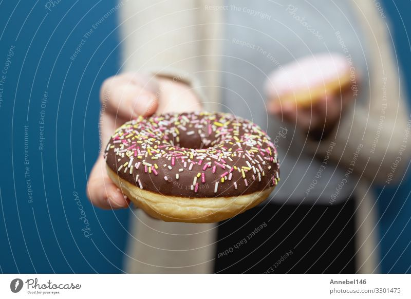 Frau hält einen köstlichen bunten Donut-Streusel in der Hand Dessert Frühstück Diät Haut Erwachsene Finger lecker gelb rosa schwarz weiß Krapfen süß Snack
