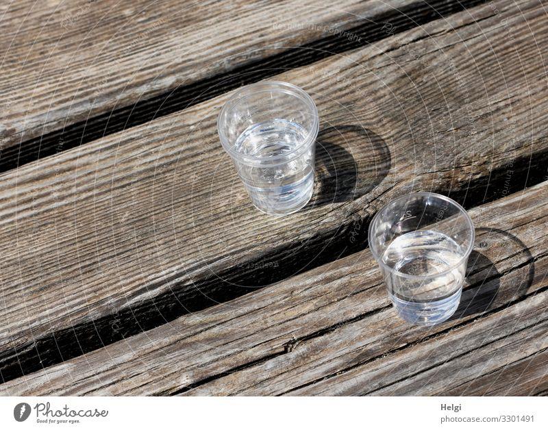 zwei Plastikbecher mit Schnaps stehen auf einem Holztisch Getränk Alkohol Spirituosen Glas trinken warten authentisch einfach klein lecker braun grau
