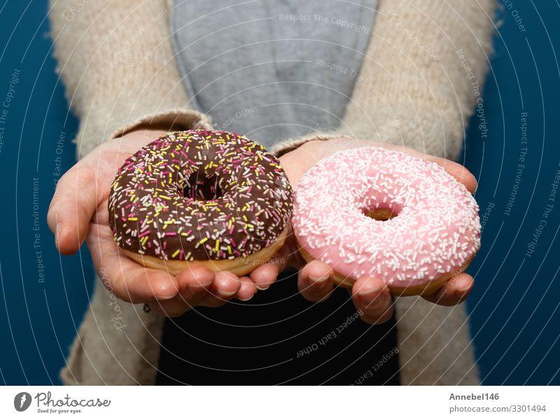 Frau hält einen köstlichen bunten Donut Dessert Frühstück Diät Haut Erwachsene Hand Finger lecker gelb rosa schwarz weiß Krapfen süß Snack vereinzelt