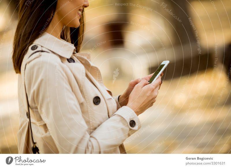 Fröhliche junge Frau mit Handy im Herbstpark Lifestyle schön ruhig Telekommunikation Telefon Technik & Technologie Mensch feminin Junge Frau Jugendliche
