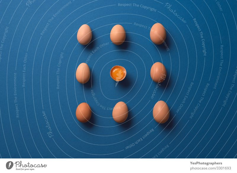 Ganze Eier und ein geknacktes Eigelb. Bio-Braune Eier Ernährung Diät Gesunde Ernährung frisch natürlich obere Ansicht ausgerichtet Blauer Hintergrund