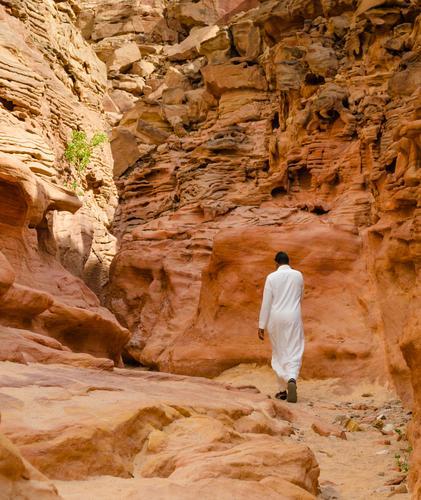 Mann in weißer arabischer Kleidung wandert in einer farbigen Schlucht in Ägypten exotisch Ferien & Urlaub & Reisen Tourismus Sommer Berge u. Gebirge Mensch