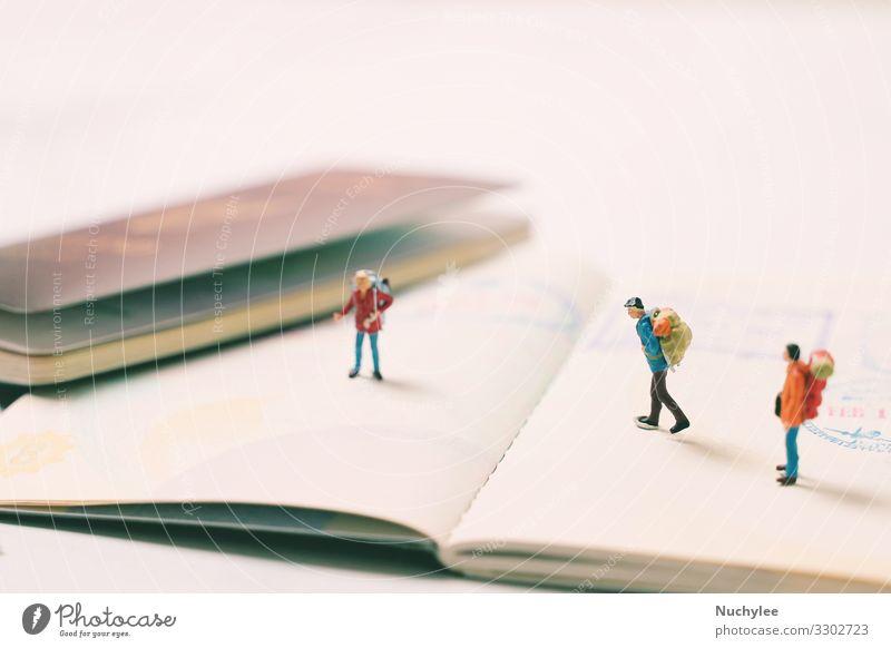 Miniatur-Personenfiguren mit Rucksack im Gehen und Stehen auf dem Reisepass Abenteuer Hintergrund Backpacker Rucksacktourismus Mitteilung Konzept kreativ