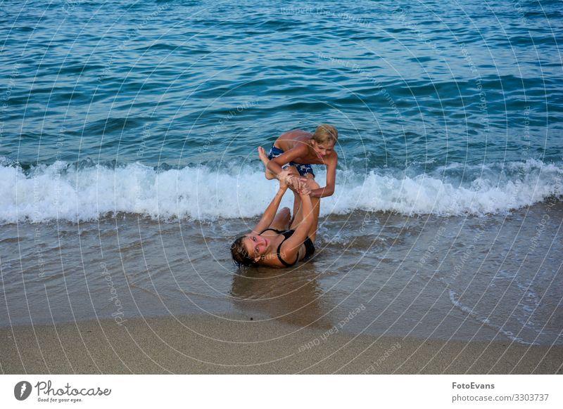 Zwei lustige Kinder spielen gemeinsam an einem Strand vor einer Meereswelle zwei Geschwister Bruder und Schwester Sandstrand MEER Menschen kämpfen Spaß Freude
