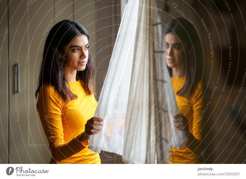 Perserin beim Blick durch das Fenster Lifestyle Glück schön Haare & Frisuren Gesicht Erholung Winter Wohnung Mensch feminin Junge Frau Jugendliche Erwachsene 1