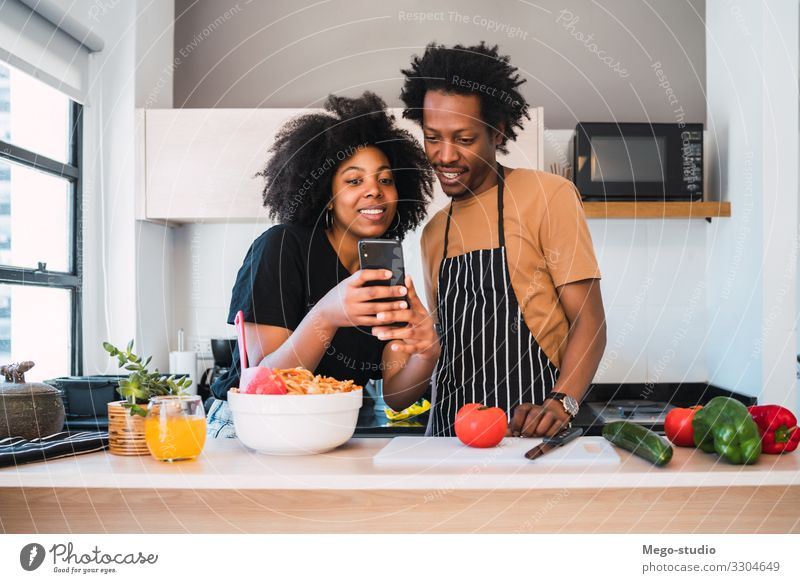 Ein Afro-Paar, das zusammen kocht und zu Hause telefoniert. Lifestyle Glück Freizeit & Hobby Wohnung Küche Telefon Handy Frau Erwachsene Mann Afro-Look Lächeln