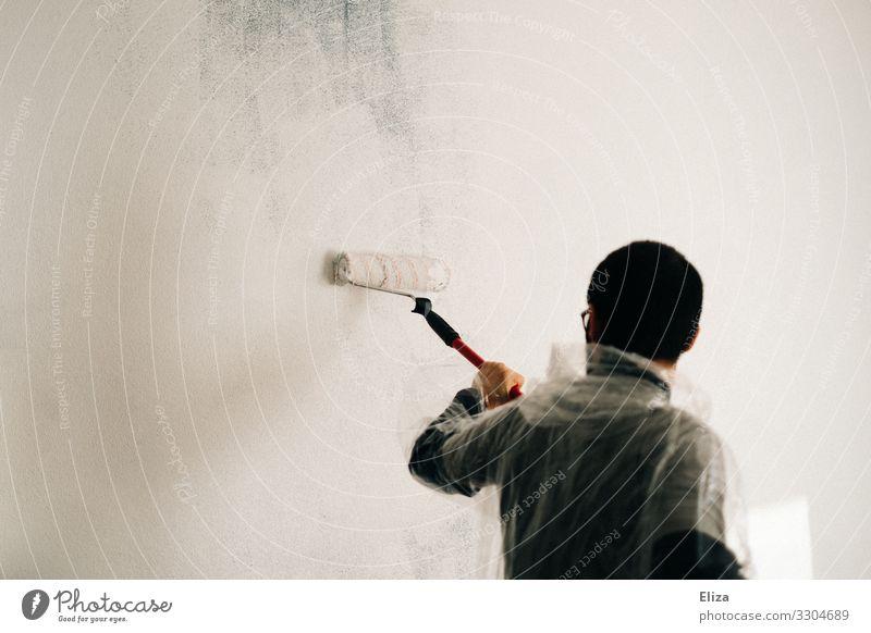Ein Mann streicht eine Wand mit einer Farbrolle in weißer Farbe Streichen renovieren Maler anstreichen Auszug Anstreicher Anstrich Erwachsene überstreichen
