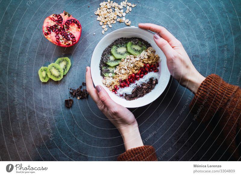 Frauenhände halten eine Smoothie-Schüssel mit veganen Zutaten. Joghurt Frucht Dessert Frühstück Vegetarische Ernährung Diät Schalen & Schüsseln Mensch