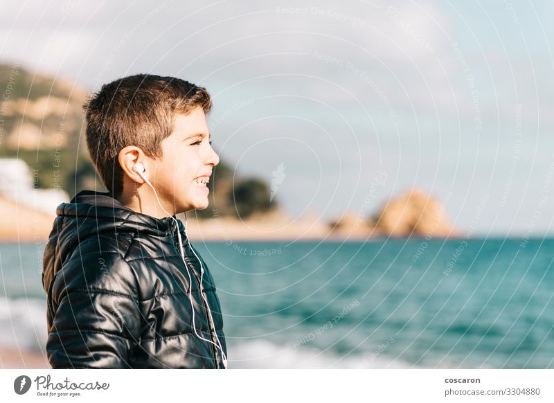 Süßes kleines Kind, das mit einem Kopfhörer Musik hört Lifestyle Freude Glück schön Erholung Freizeit & Hobby Ferien & Urlaub & Reisen Tourismus Ausflug Strand
