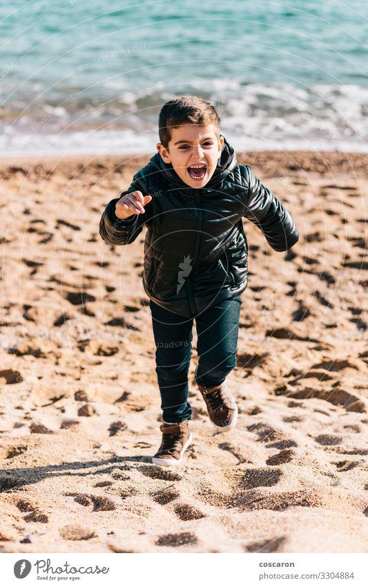 Kleines Kind rennt an einem Wintertag am Strand Lifestyle Freude Glück schön Leben Freizeit & Hobby Spielen Ferien & Urlaub & Reisen Freiheit Meer Mensch