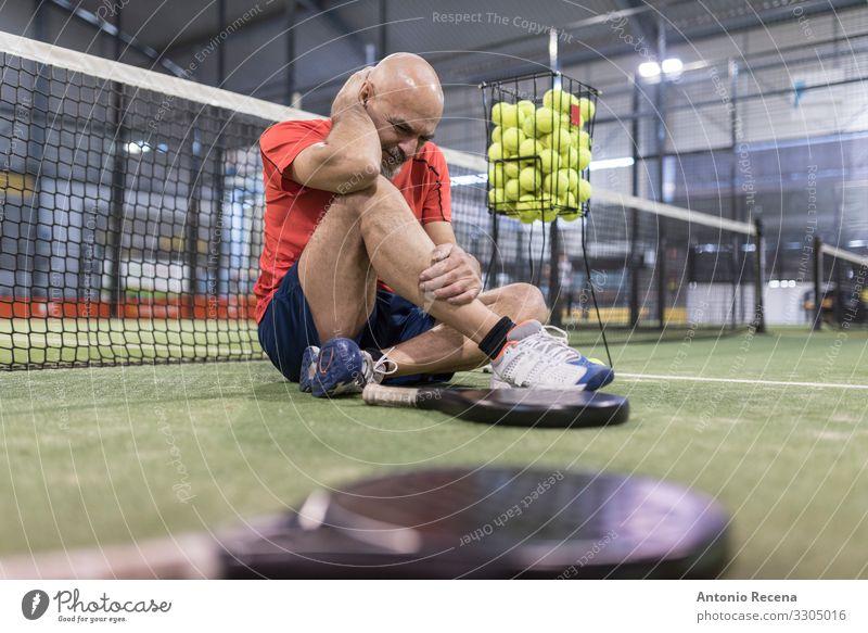 älterer Mann spielt Paddle-Tennis auf dem Platz Spielen Sport Erwachsene Glatze Vollbart alt sitzen Müdigkeit Schmerz Konkurrenz Senior Paddeltennis Padel