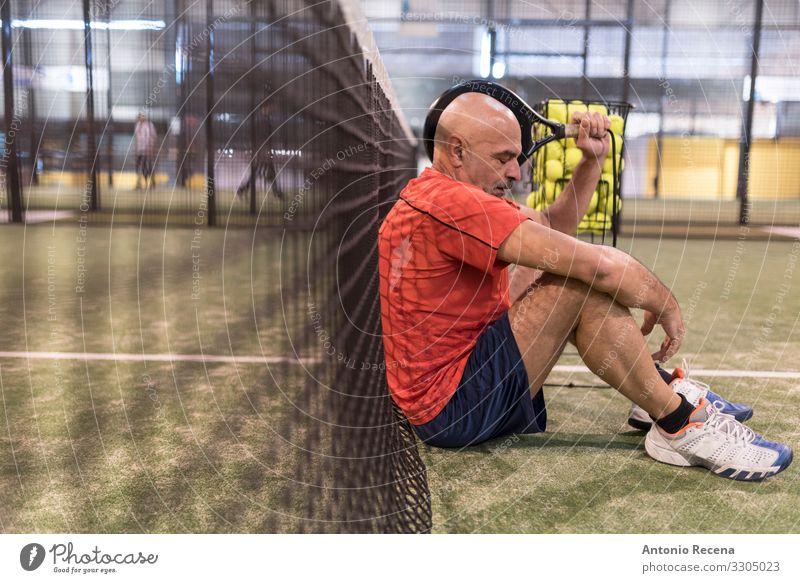 älterer Mann spielt Paddle-Tennis in der Halle, er ist müde Spielen Sport Erwachsene Glatze Vollbart alt Konkurrenz Senior Paddeltennis Padel Gerichtsgebäude