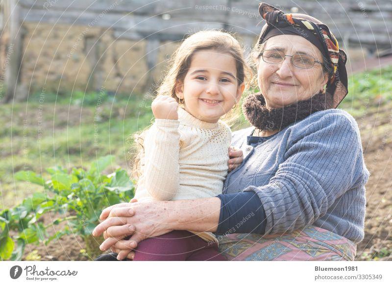 Porträt eines glücklichen kleinen Mädchens mit seiner älteren Großmutter Lifestyle Stil Spielen Garten Muttertag Kind Mensch Frau Erwachsene Weiblicher Senior