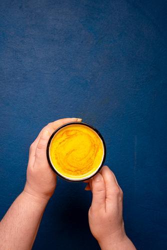 Kurkuma-Latte in der Hand halten. Entgiftendes Kurkumagetränk. Goldene Milch Kräuter & Gewürze Getränk gelb Kurkuma-Langhaar obere Ansicht Antioxidans