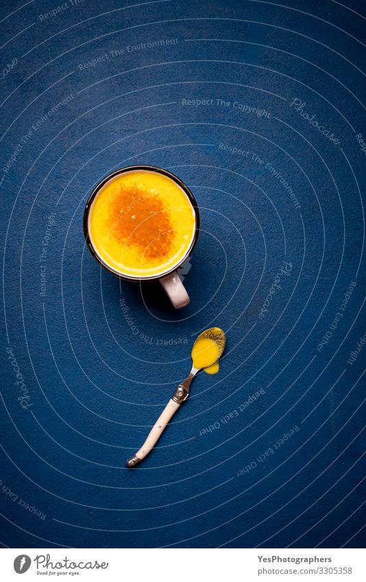 Kurkuma-Latte auf einem blauen Tisch. Gesundes Getränk. Gelber Milchbecher Kräuter & Gewürze Heißgetränk natürlich Kurkuma-Langhaar obere Ansicht Antioxidans