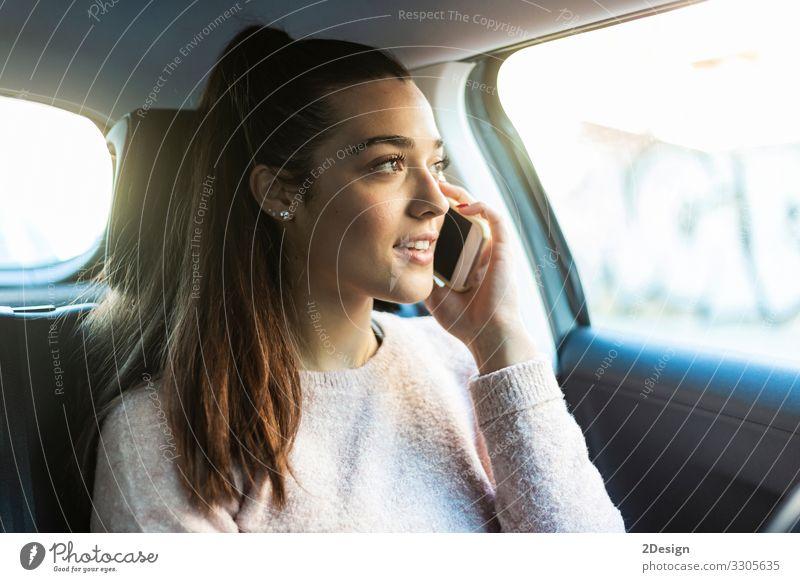 Junge schöne Frau mit Pferdeschwanz telefoniert auf dem Rücksitz eines Autos PKW sprechend Handy Business hübsch urban gefesselt Mädchen Menschen niedlich