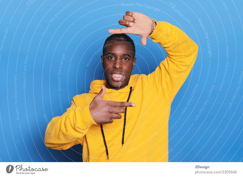 Mann in warmem Freizeitpullover, der mit den Händen einen Rahmen für die Herstellung von Pullovern herstellt Lifestyle Gesicht Fotokamera Mensch maskulin