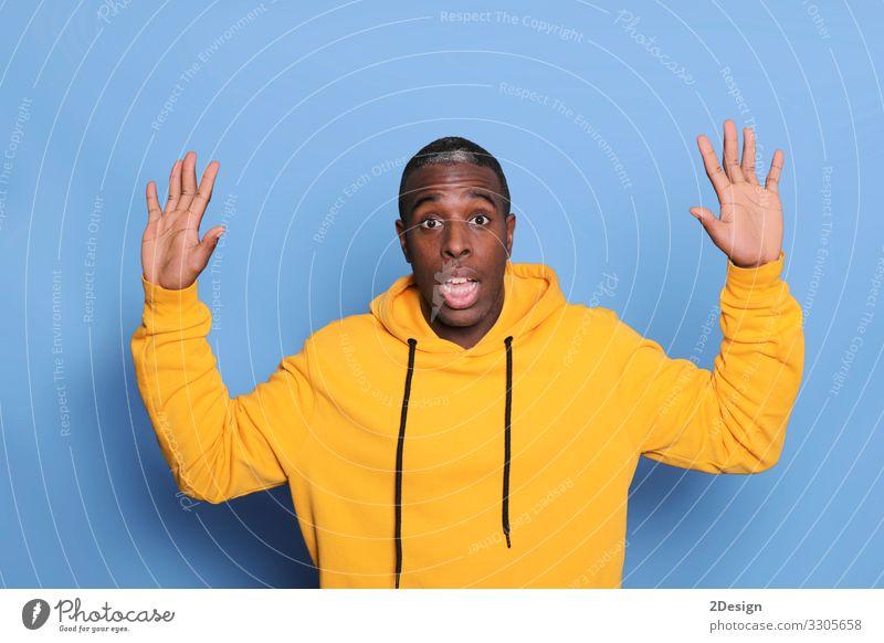 Ein junger attraktiver Mann schaut überrascht und isoliert auf blauem Hintergrund Glück Gesicht Mensch maskulin Junger Mann Jugendliche Erwachsene 1 18-30 Jahre