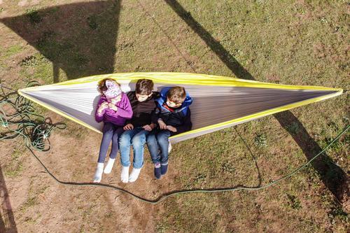 Drei Kinder, die sich auf einer Hängematte entspannen. Ansicht aus der Luft Freude Glück schön Erholung ruhig Freizeit & Hobby Spielen Sommer Sommerurlaub