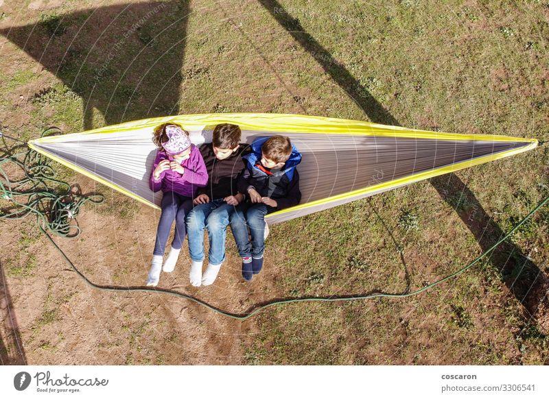 Drei kleine Kinder sitzen auf einer Hängematte Freude Glück schön Erholung Windstille Freizeit & Hobby Spielen Sommer Sommerurlaub Garten Mensch Kleinkind