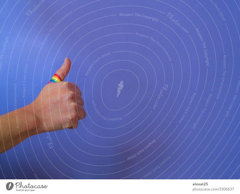 Daumen hoch mit Regenbogenband auf Lila - Positives Schwulenkonzept Freiheit Erfolg Business Homosexualität Arme Hand Finger Fahne gut Lebensfreude Akzeptanz
