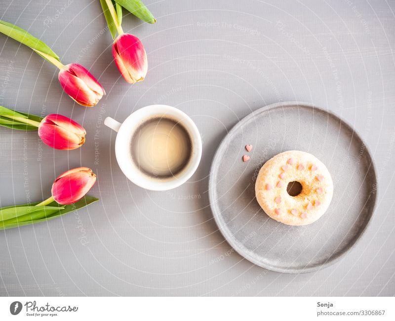 Rosa Tulpen mit einer Tasse Kaffee und einem Donat Lebensmittel Teigwaren Backwaren donat Ernährung Frühstück Kaffeetrinken Getränk Heißgetränk Teller Lifestyle