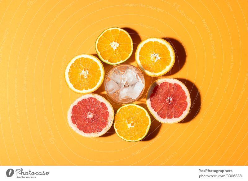 Zitrusfrüchte und Glas mit Eis im Sonnenlicht. Frucht Orange Frühstück Bioprodukte Vegetarische Ernährung Diät Erfrischungsgetränk Gesunde Ernährung hell rot