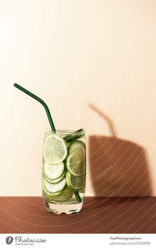 Gurken- und Limettenwasser. Kalte grüne Limonade. Frucht Getränk Erfrischungsgetränk Glas Trinkhalm rot antioxidatives Getränk Brauntöne Textfreiraum