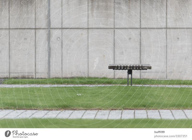 minimalistische Ansicht einer Bank mit Rasen vor Betonwand Gras Gebäude Mauer Wand Parkbank Holz Linie warten ästhetisch außergewöhnlich modern Stadt grau grün
