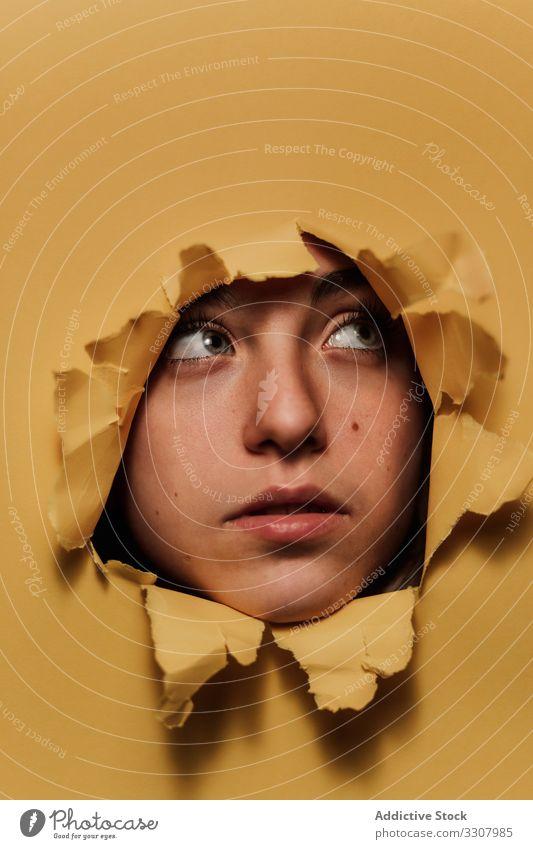 Nachdenklicher weiblicher Teenager schaut aus einem Loch im Atelier herausschauen Golfloch Frau Frisur zuschauen zerrissen Papier gelb jung Schönheit ernst