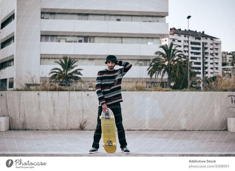 Junger stilvoller Mann mit Skateboard in der Stadt stehend Schlittschuh Straße Großstadt Gebäude Hipster stylisch jung modern Zeitgenosse aktiv männlich urban