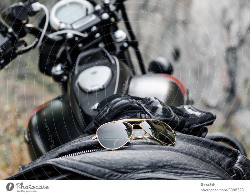 Sonnenbrille und Handschuhe am Motorrad-Treibstofftank Stil Verkehr Mode Bekleidung Leder Accessoire Glas Metall braun mehrfarbig grau schwarz Schutz Munition