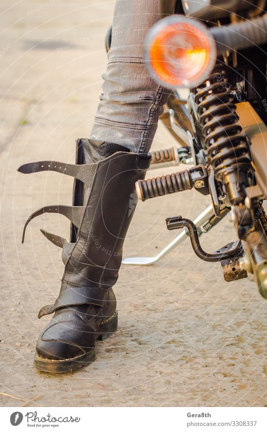 Fuß eines Biker-Mädchens in einem Motorradstiefel Stil Schuhe sitzen Schutz Motorradfahren Biker-Mädchenfuß Körperteil Jeans Stiefel Mädchenbein Grunge Bein