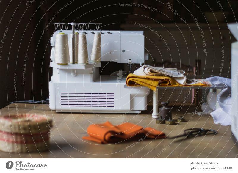 Arbeitsplatz einer Schneiderin mit Nähmaschine Textil Stoff Tisch Innenbereich Mode Material Schneidern Industrie Atelier Werkstatt Faser Gerät heimwärts Gewebe