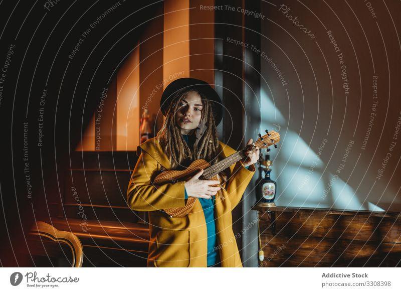 Stilvolle junge Frau spielt Gitarre spielen Hipster Musik stylisch ernst tausendjährig Ukulele hawaiianisch stehen fokussiert konzentriert praktizieren Musiker