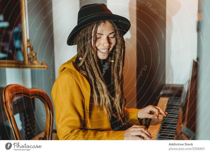 Hipster tausendjährige Frau spielt Klavier spielen Rastalocken Musik stylisch sitzen fokussiert konzentriert praktizieren Musiker Instrument Kunst Pianist