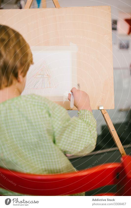 Kind zeichnet zu Hause auf Leinwand zeichnen Bild Junge Kunst ernst Windstille Farbe Hobby heimwärts friedlich lässig Kindheit Appartement flach kreativ