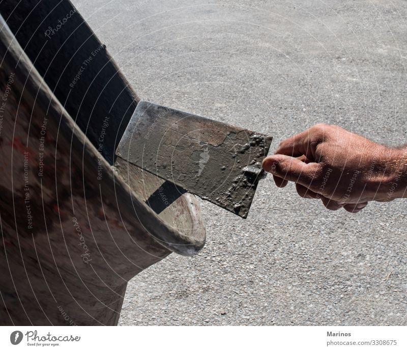 Zementmischer und eine Hand, die eine Kelle hält. Arbeit & Erwerbstätigkeit Industrie Business Werkzeug Maschine Gebäude Beton Metall alt machen Mixer
