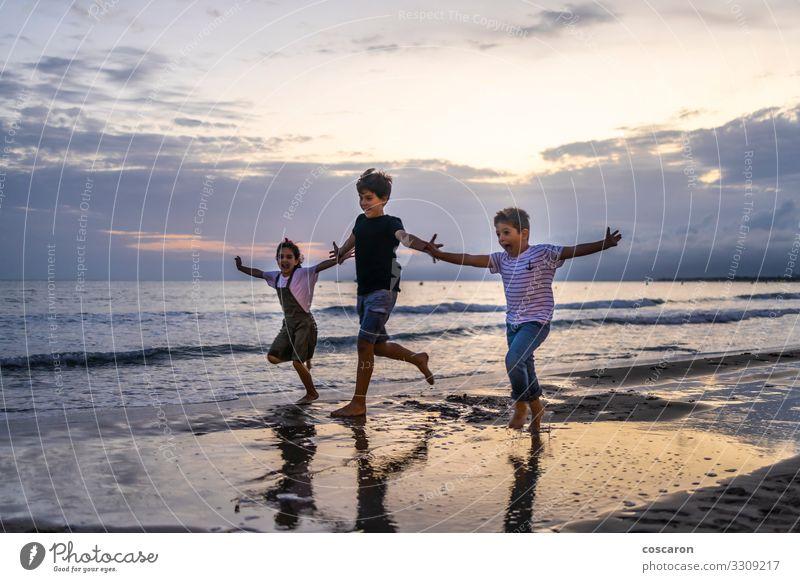 Drei Kinder laufen bei Sonnenuntergang am Strand Lifestyle Freude Glück Erholung Freizeit & Hobby Spielen Ferien & Urlaub & Reisen Abenteuer Freiheit Sommer