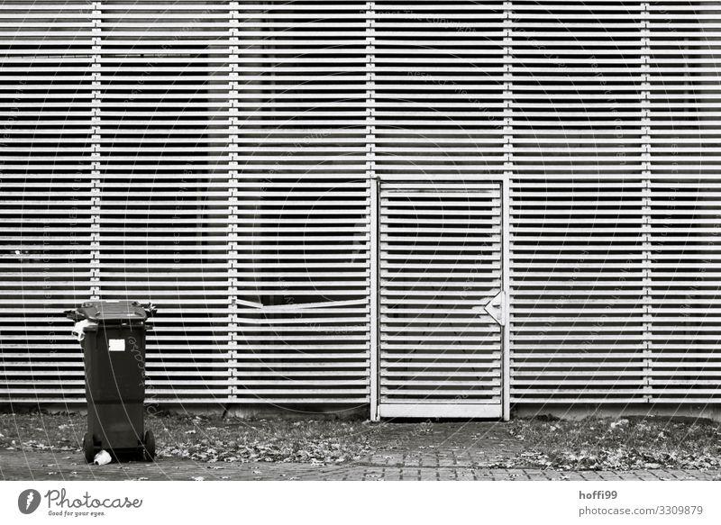 trostlose Linienfassade mit Tür, Mülltonne und Knick Studium Industrieanlage Gebäude Architektur Mauer Wand Fassade Müllbehälter warten ästhetisch dreckig